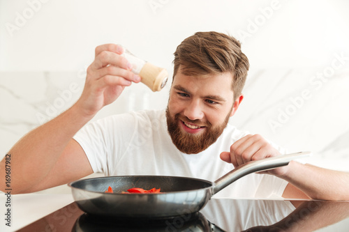 Smiling bearded man sprinkle with salt of vegetables - 169687982
