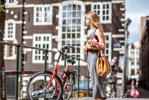 Young beautiful woman walking with bouguet of tulips on the bridge with bicycles over the water channel in Amsterdam old city