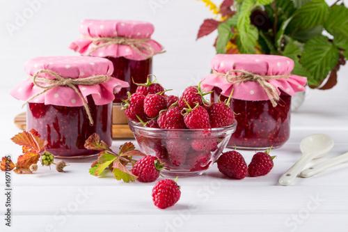 Homemade raspberry jam for breakfast and fresh raspberry on white wooden table
