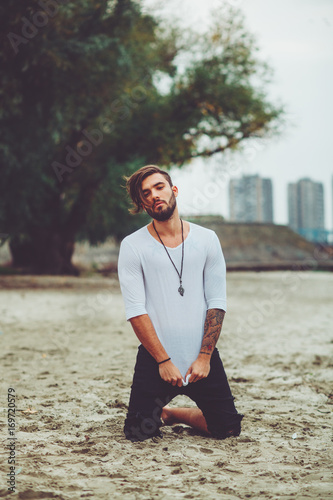 Fotobehang Kapsalon Handsome man kneeling on the sand by the river