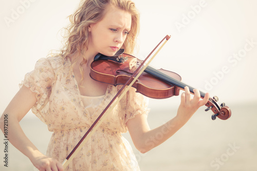 Fotobehang Muziek Woman playing violin on violin near beach
