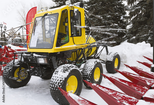 Yellow tractor seeder on winter snow Poster