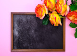 empty black frame and a bouquet of yellow roses