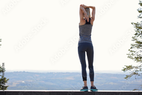 Woman stretching before workout outdoors on summer day. Jogging, sport, fitness, active lifestyle concept