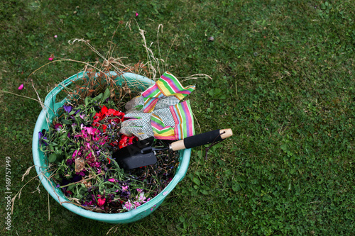 A Green Plastic Garden Basket With Waste Trowel And Gloves
