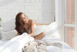 Young sexy woman sitting on bed in light bedroom.