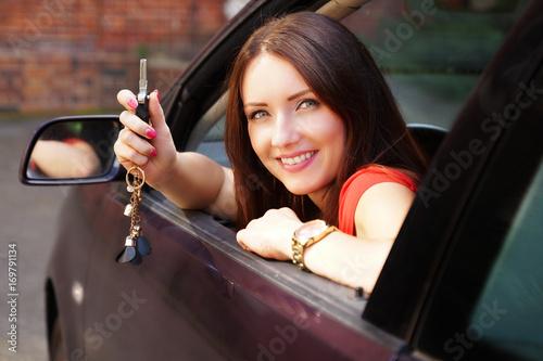 Frau hält Autoschlüssel aus dem Fenster Poster