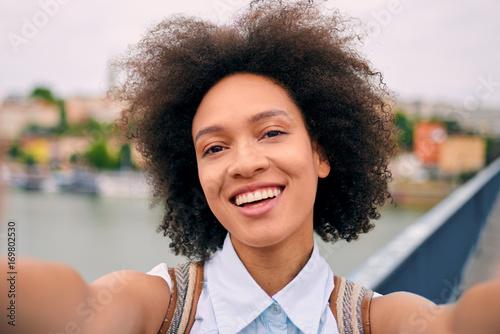 Mixed race tourist taking selfie on a bridge