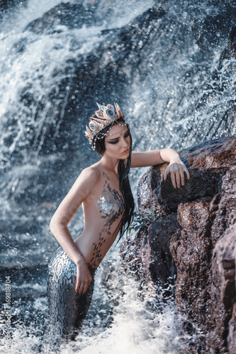The real mermaid is resting on the ocean shore. Silver tail, the body is covered with scales. Creative colors