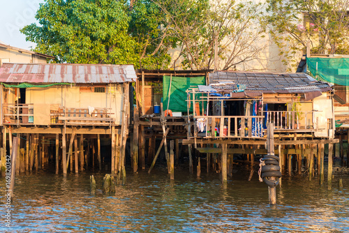 Fotobehang Thailand Stilt houses along the Chao Phraya river in the megacity Bangkok. In many parts, the simple houses have been demolished and are replaced from expensive apartments
