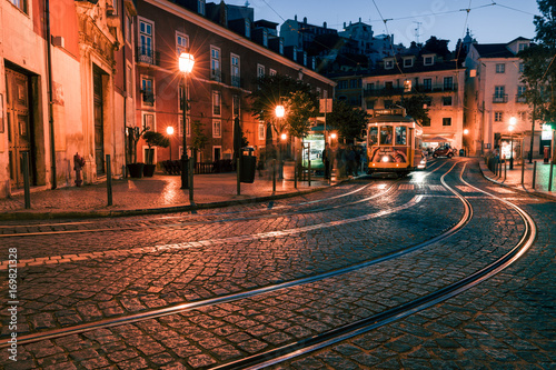 Traditional yellow tram at the old night streets of Lisbon Plakat