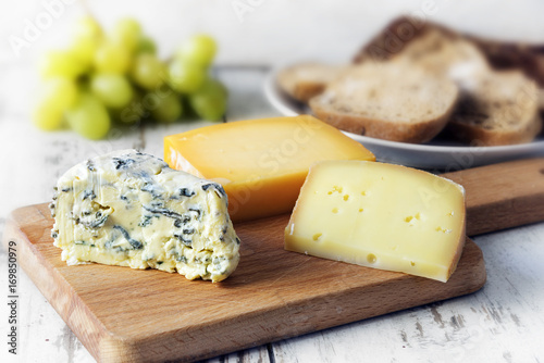 Poster various cheese on a wooden board, bread and grapes blurred in the bright rustic