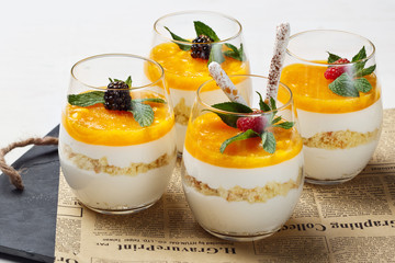 Orange cheesecake in glasses on old  background