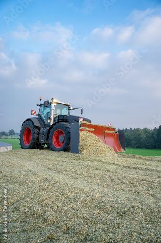 Fotobehang Trekker Traktor planiert Maishaufen, Hochformat