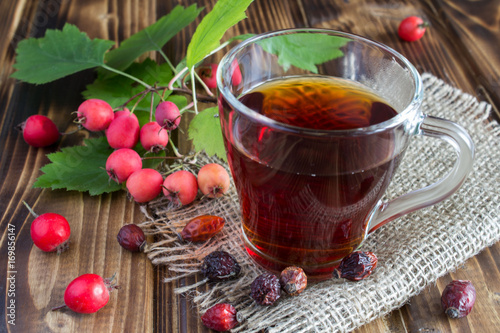 Fototapeta Tea with dogrose the wooden background