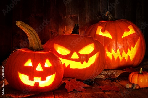 Fotobehang Herfst Halloween night scene with a group of spooky Jack o Lanterns against a wood background