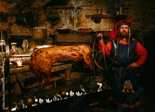 Medieval man doing roasted pig on the rack