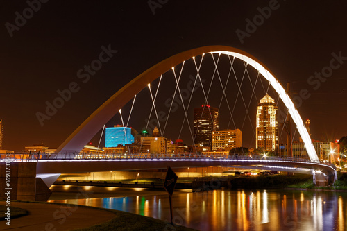 One of the central features of Des Moines is the Iowa Women of Achievement Bridge that spans the Des Moines River. Through the lit arch, the skyline of Des Moines is clearly visible.