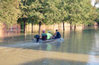 People in a motor boat ride down the flooded Houston street. Consequences of the Hurricane Harvey, Texas, USA