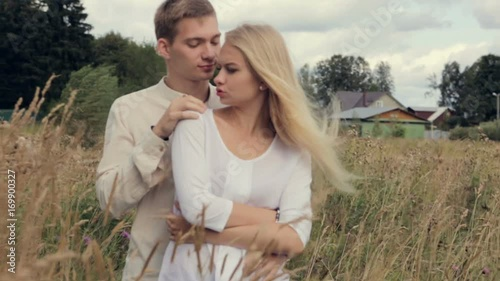 Young couple in love standing in the field and hugging. © rewerbox