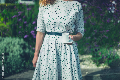 Young woman with cup of coffee in garden Poster