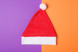 Santa Claus red hat on orange and wiolet paper background , minimal style.