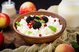 Cottage cheese with blackberries in a  bowl. - 169943786