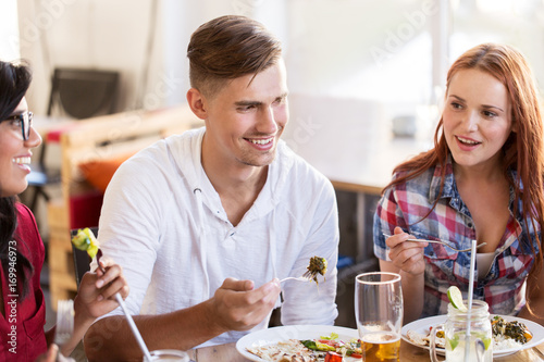 happy friends eating and talking at restaurant - 169946973