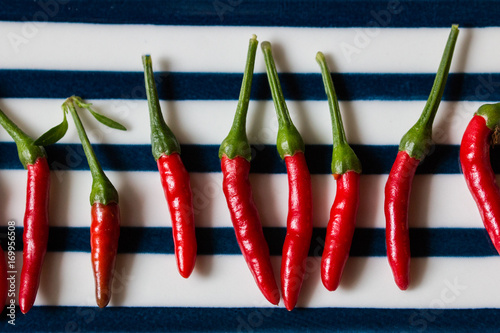 Fotobehang Hot chili peppers Red hot peppers on blue striped plate