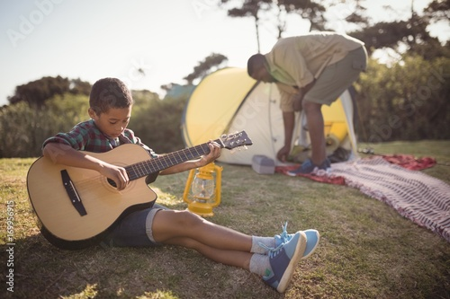 Foto op Aluminium Milkshake Boy playing guitar while father setting up a tent in background