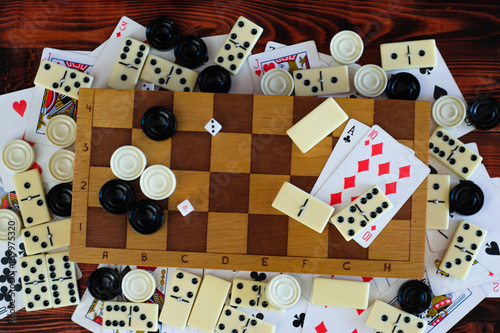 Various board games chess board, playing cards, dominoes Poster