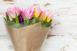 Tulips wrapped on brown paper on light background - 169988141