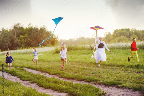 happy children in summer nature, flying a kite