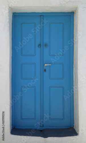 Fotobehang Santorini blue door of a home built into the volcanic rock hillside on the island of Santorini, Greece