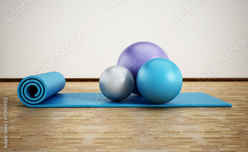 Fototapeta Pilates mat and exercise balls standing on parquet floor. 3D illustration