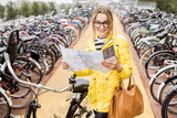 Young woman in yellow raincoat standing with tourist map on the bicycle parking in Amsterdam - 170017375