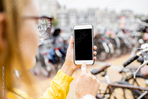 Holding a smart phone with empty screen to copy paste on the bicycle parking background