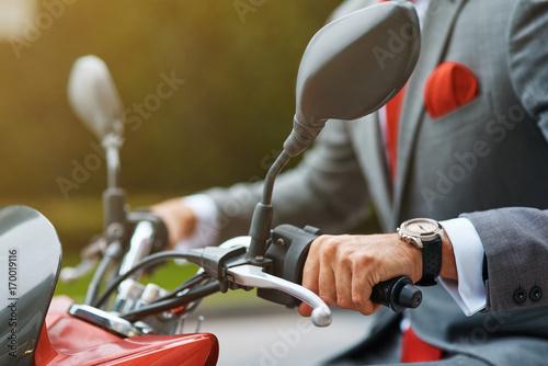 Close up of a businessman ricing a motorbike