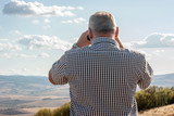 Uomo ammira il paesaggio con il binocolo