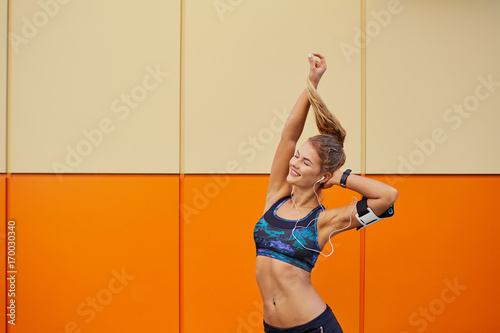 Sportive positive girl raised her hands up listening to music in headphones on an orange background.