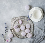 Macarons in bowl and on table with cup and lavender.