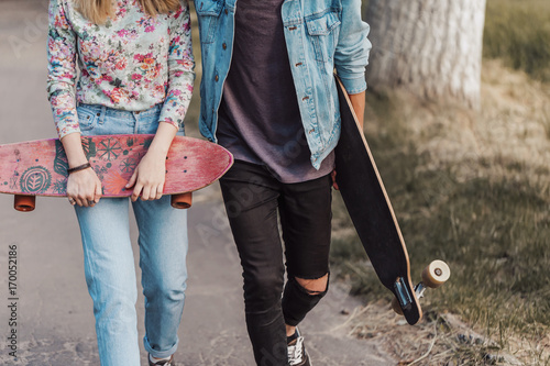 Fotobehang Skateboard Boy and girl, hipster stylish teenagers wearing sunglasses are walking through the park holding skateboards in hands, teen freedom concept