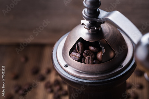 Coffee beans in coffee grinder on wooden background
