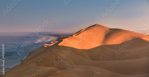 Fotobehang Diepbruine andwich harbour, high dunes of the Namib desert reaching the Atlantic ocean