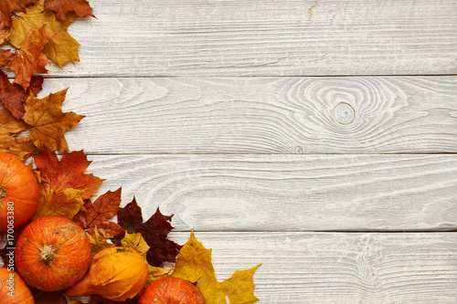 Autumn leaves and pumpkins over old wooden background - 170063380