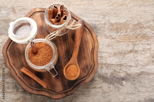 Fotobehang Kruiden 2 Composition with cinnamon sugar in glass jar on wooden board