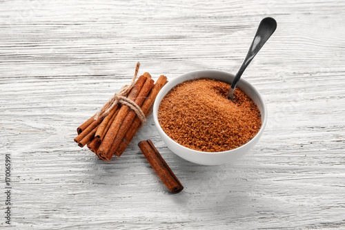 Fotobehang Kruiden 2 White bowl with cinnamon sugar and sticks on wooden background