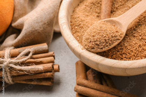 Fotobehang Kruiden 2 Cinnamon sticks and sugar in wooden bowl with spoon on grey background, closeup