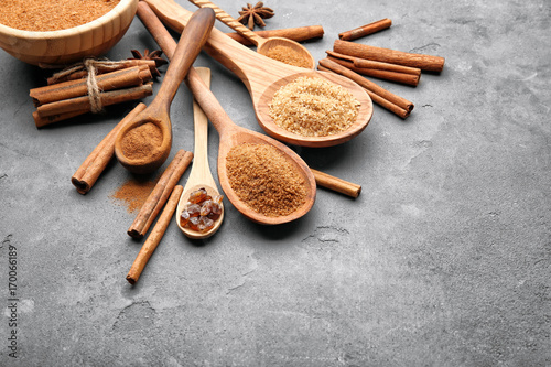 Fotobehang Kruiden 2 Composition with cinnamon sticks, sugar and powder in wooden spoons on grey background