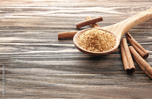 Fotobehang Kruiden 2 Composition with cinnamon sugar in spoon on wooden background